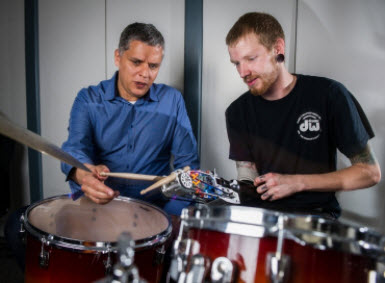 Professor Gil Weinberg and Jason Barnes, wearing prosthesis, seated behind drums
